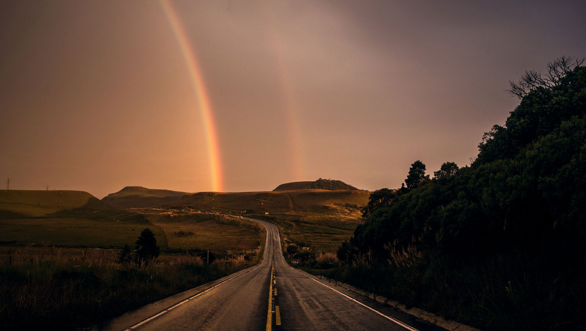 Road to the horizon with rainbow in distance