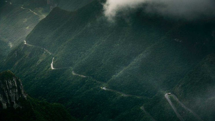 A truck journeys along a road that cuts through high mountains