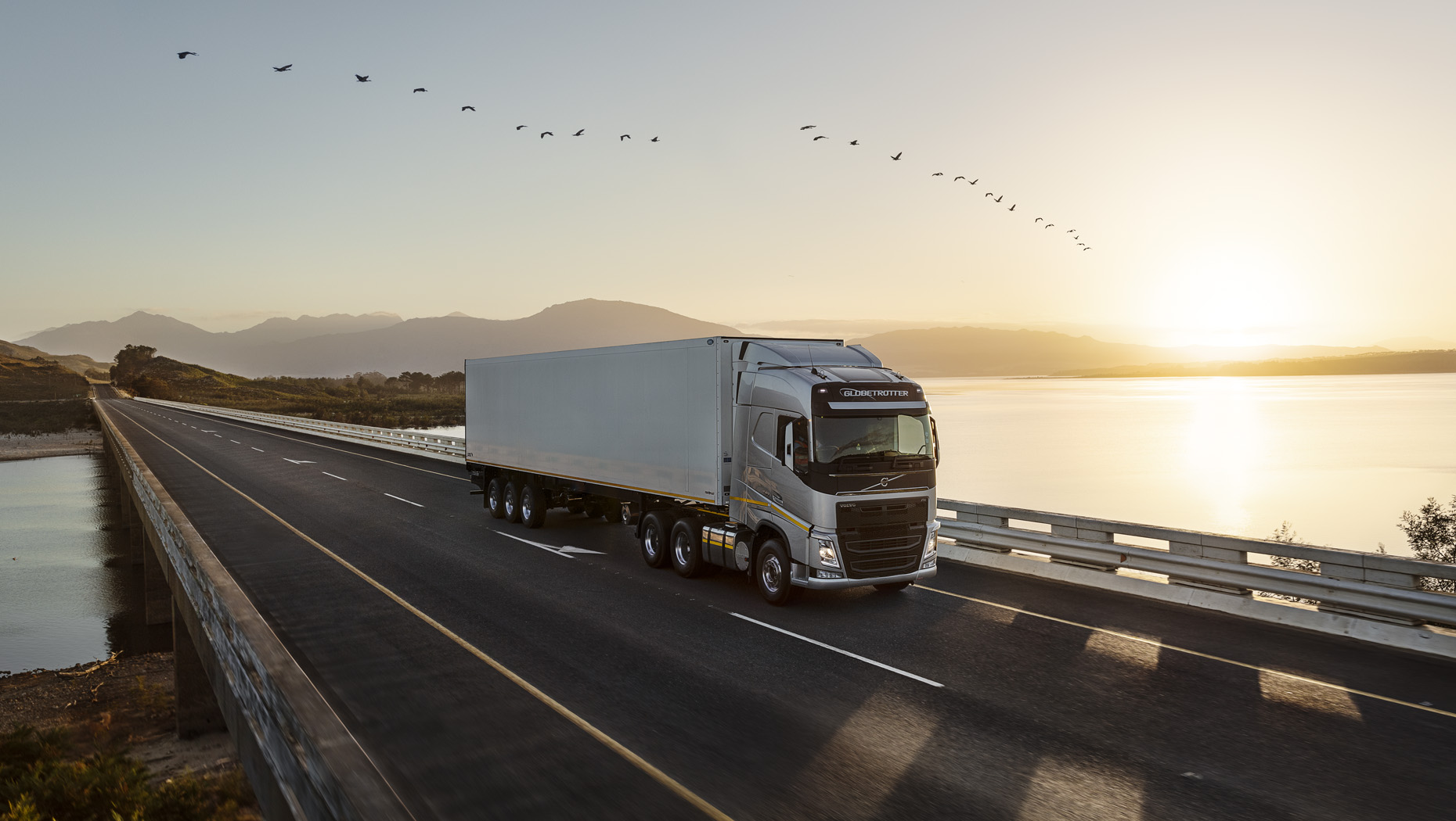 A Volvo truck driving by a lake as sun sets