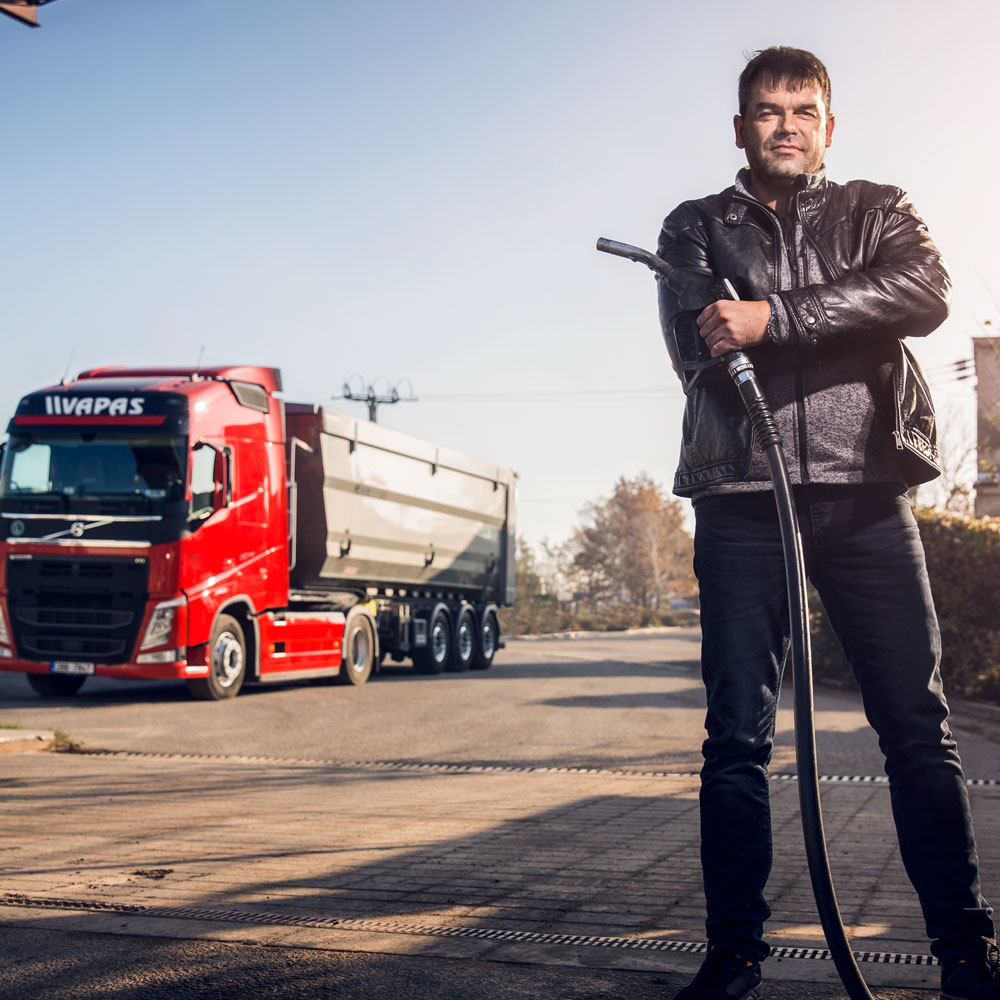 Petr Šišlák stands in the foreground holding a petrol pump with a Volvo truck behind him