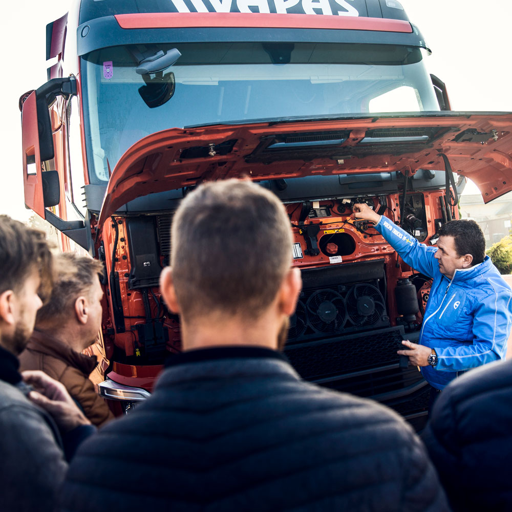 The driver trainer and several Vapas drivers stand around a truck for a training session