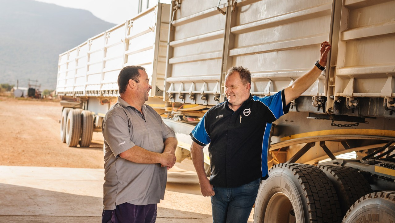 Owner Michael Vermaak and Volvo Sales Manager Koos Van Rooyen stand chatting alongside a truck trailer